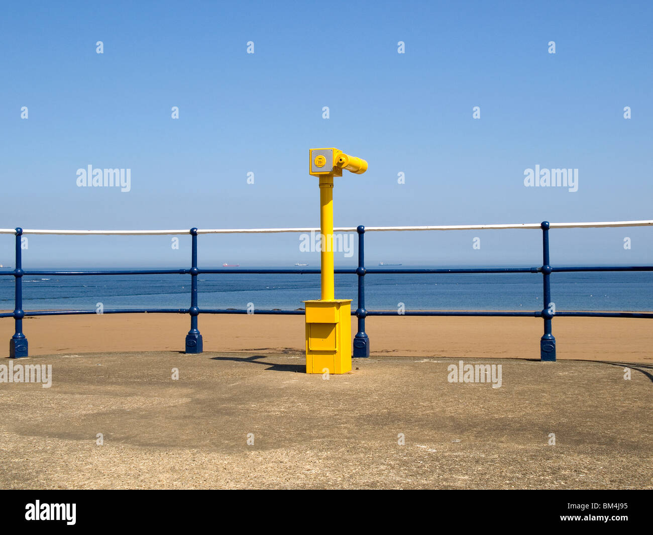 Spring at the seaside a telescope on the promenade at Redcar with distant ships - Stock Image