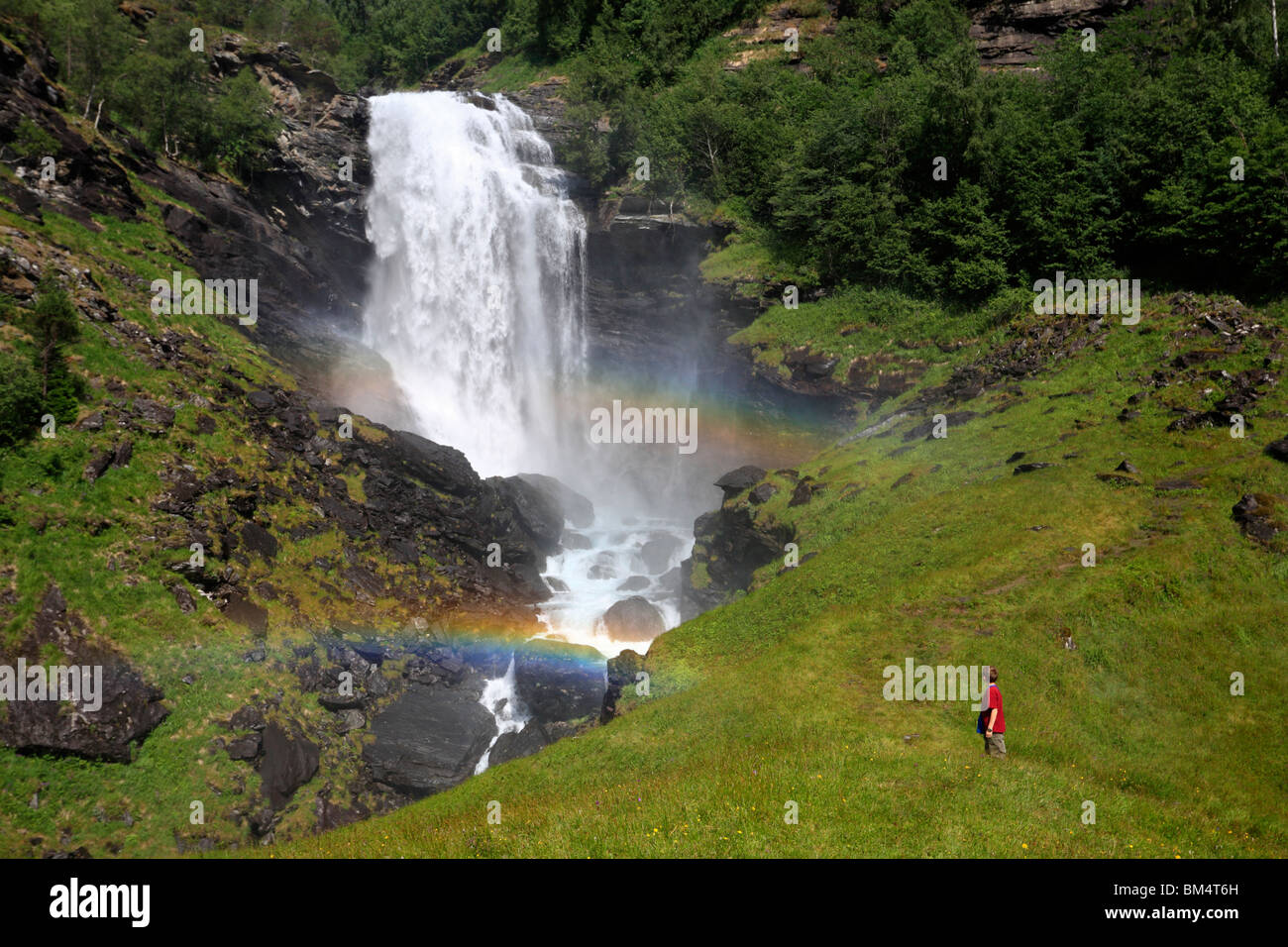 A young child gazes up in fascination at a double rainbow below a waterfall near Morkri, Sognefjord, Norway - Stock Image