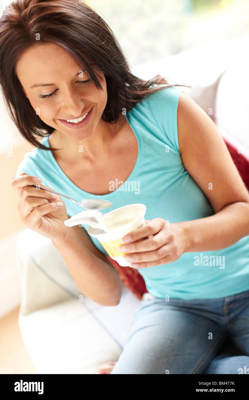 Girl eating yogurt - Stock Image