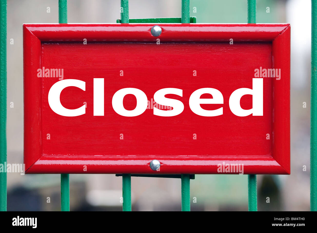 Painted red sign on a gate with the word Closed blurred background. - Stock Image