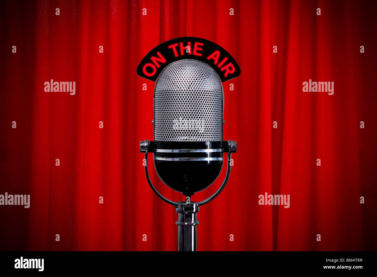Retro microphone on stage against a red curtain with spotlight effect - Stock Image