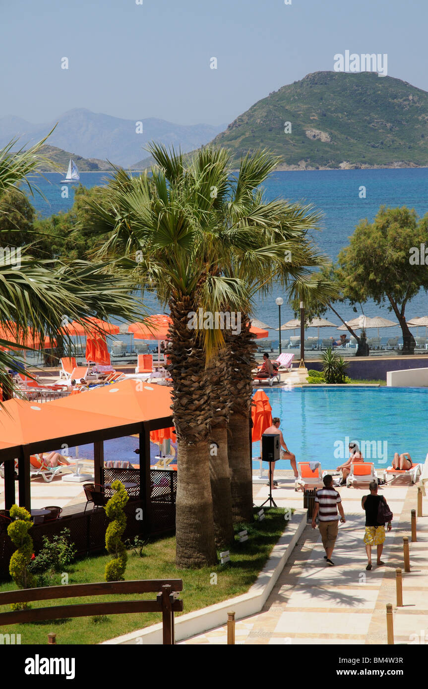 Holidaymakers relax around a hotel swimming pool in the seaside resort of Turgutreis near Bodrum Turkey - Stock Image