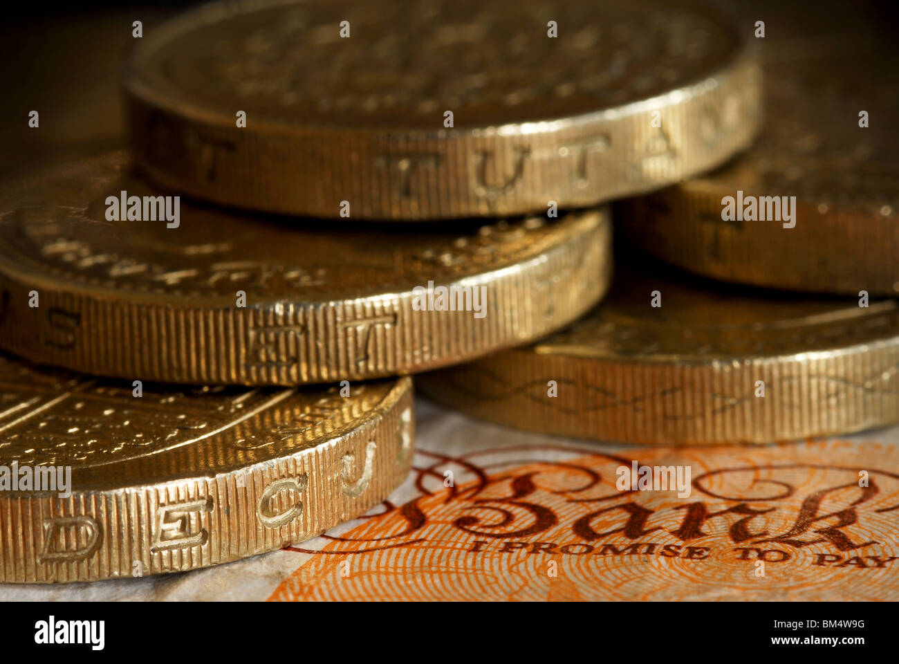 "Close up of £1 coins surrounding caption "" Bank, I promise to pay"" on £10 note Stock Photo"