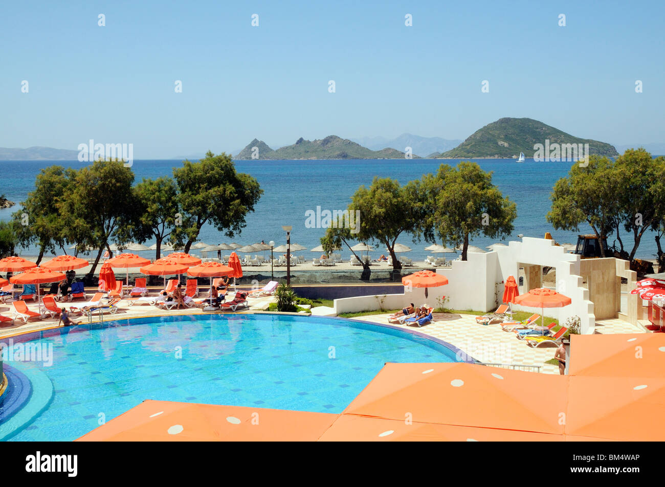 Holidaymakers relax around a hotel swimming pool in the seaside ...