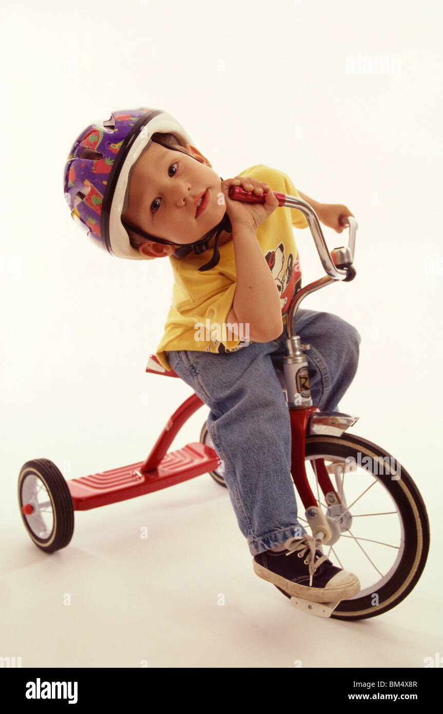 4 year old boy posing on his tricycle. - Stock Image