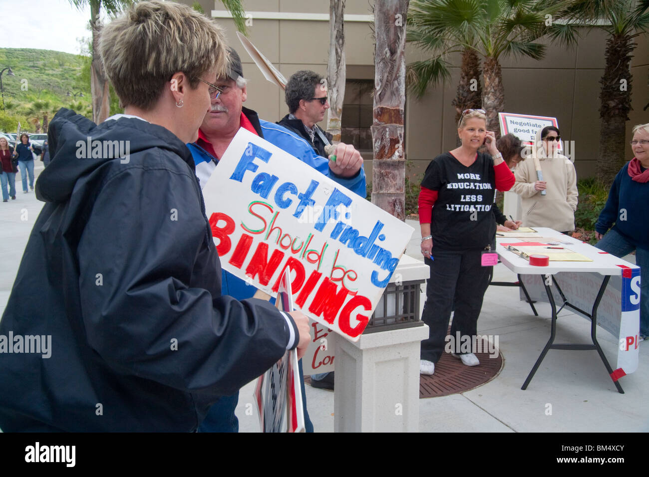 Carrying signs, protesting school teachers rally over proposed pay cuts in San Juan Capistrano, CA. Note T-shirt. - Stock Image