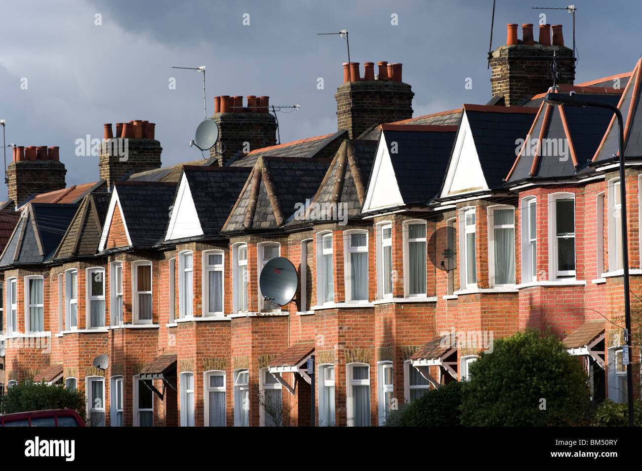 Row of terraced houses under overcast and stormy sky, London, UK - Stock Image