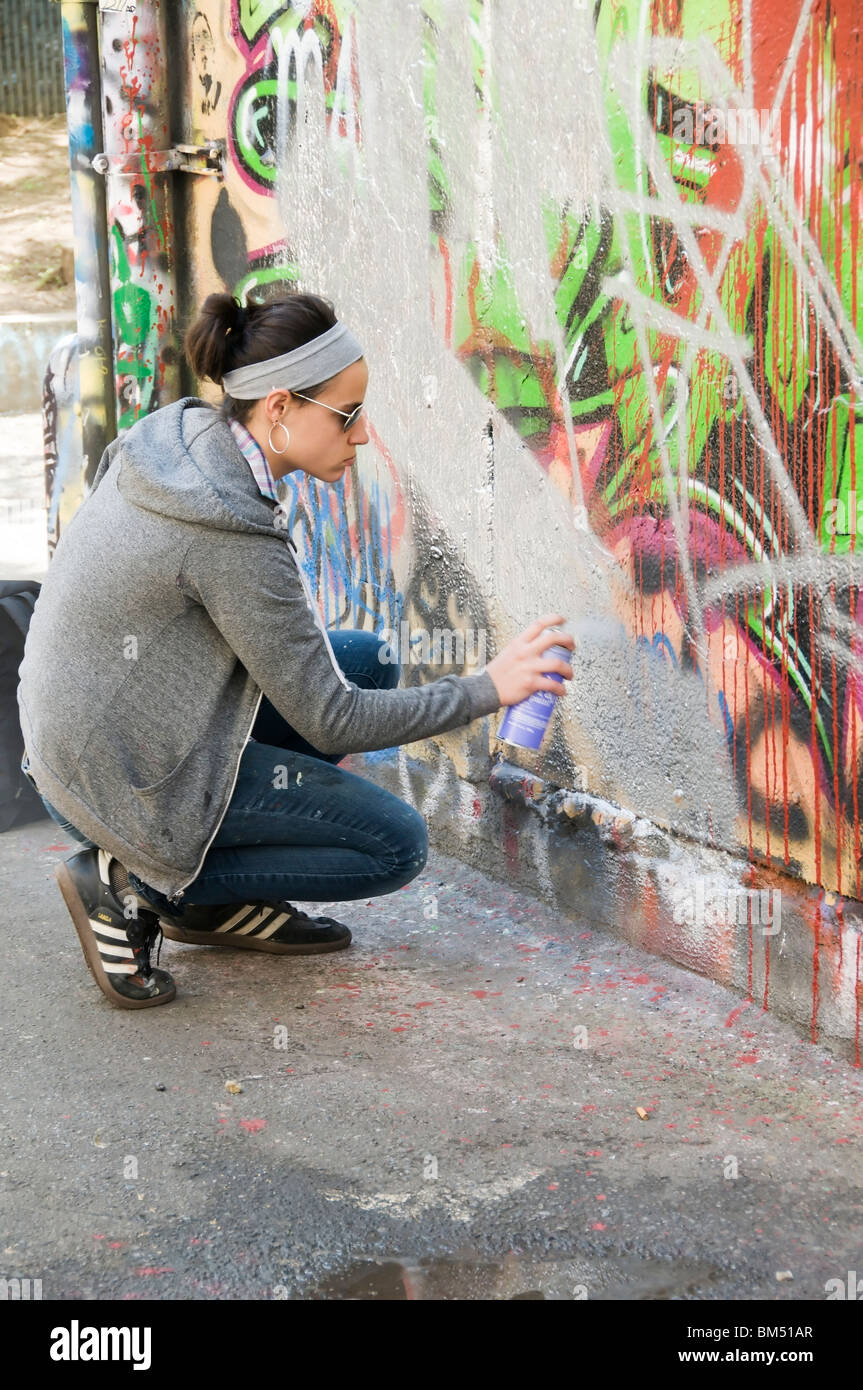 A female street artist spray paints the Capitol Theater Free Wall in downtown Olympia, Washington. - Stock Image