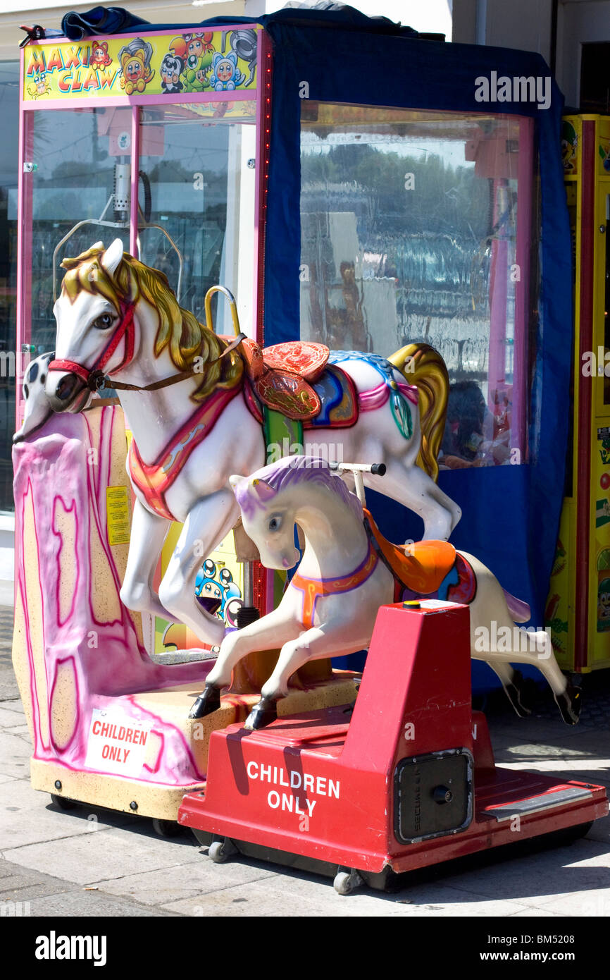 Children's Horse machine ride at an Arcade in Weymouth - Stock Image