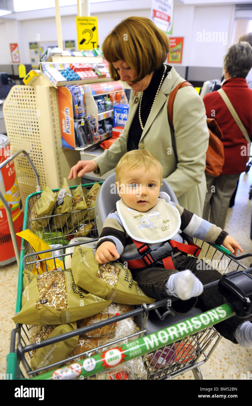 Woman shopping with baby in supermarket shopping trolley at checkout Uk - Stock Image