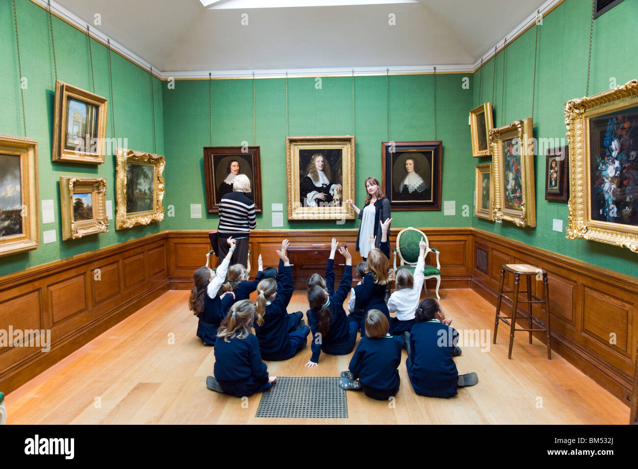 Schoolchildren raising their hands on educational school trip to The Dulwich Picture Gallery, London, England, UK - Stock Image