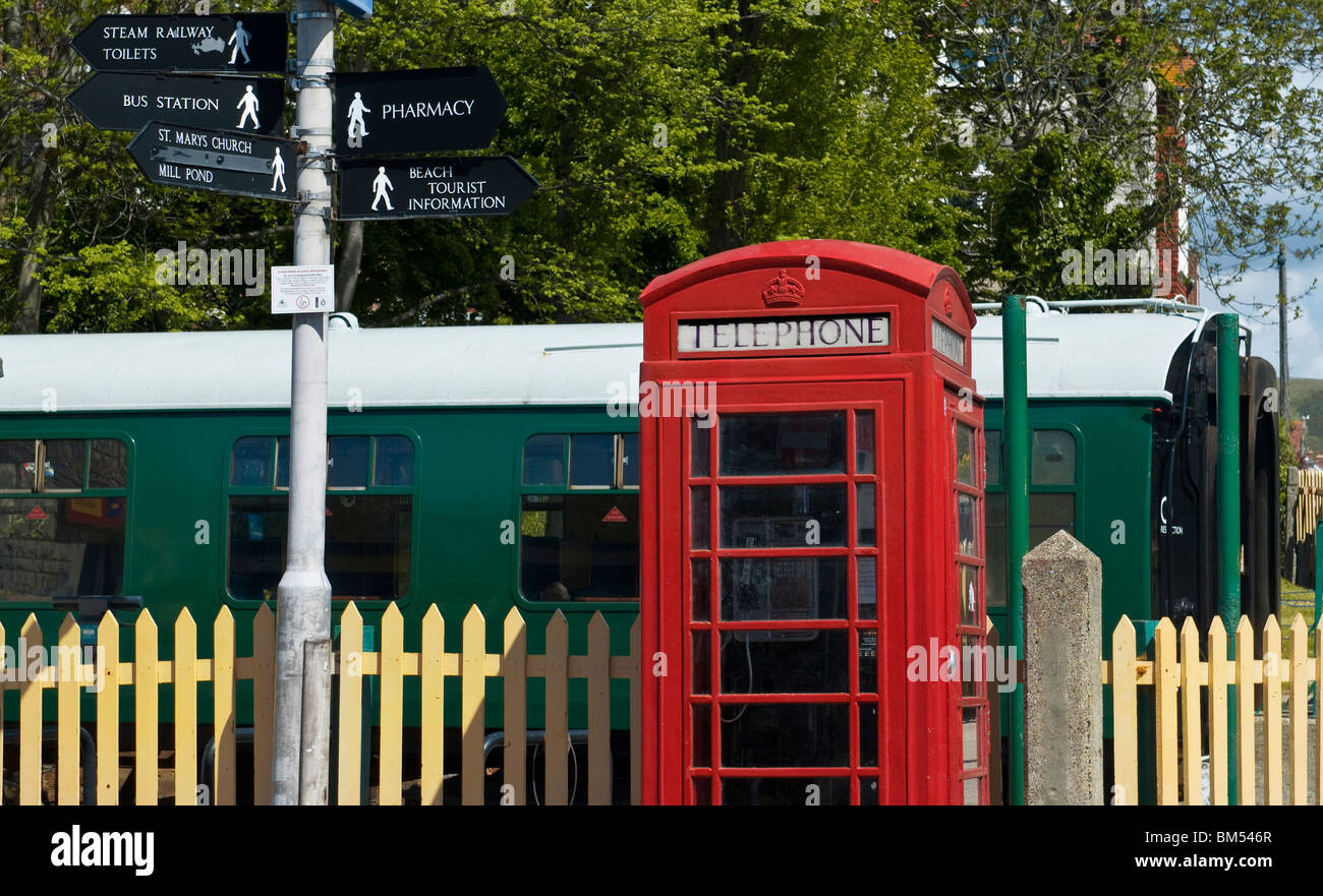 Traditional red telephone box and railway carriage at Swanage railway station Dorset UK - Stock Image