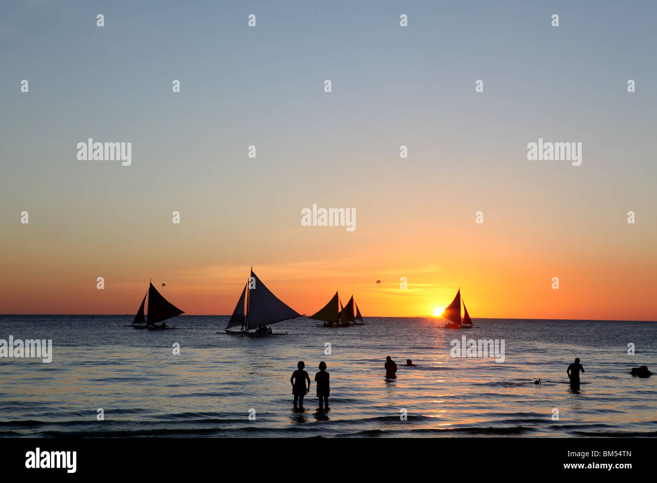 Sail boats ply the shore line at sunset on White Beach, Boracay, the most famous tourist destination in the Philippines. - Stock Image