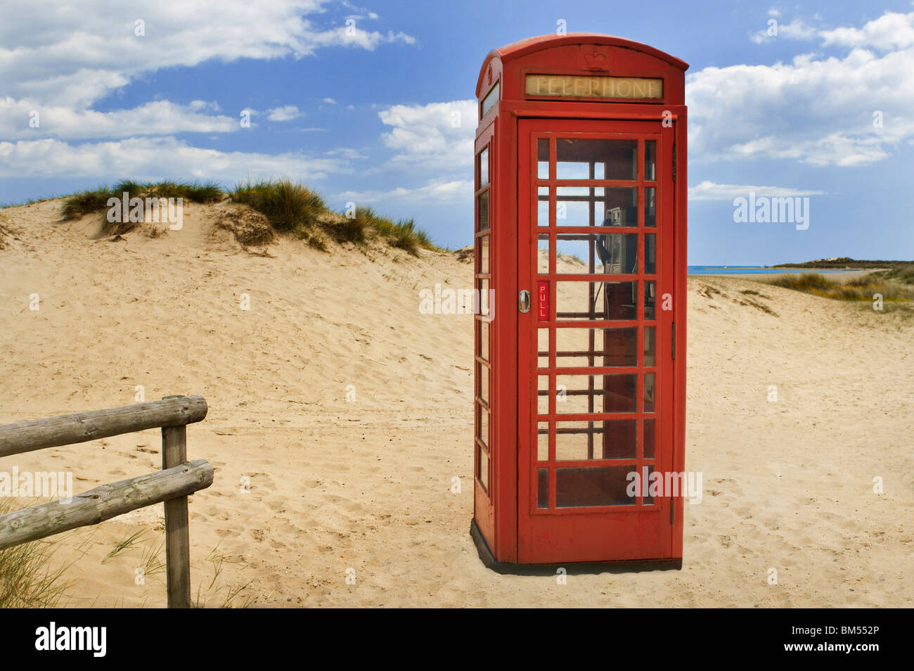 Traditional red British telephone box still in service on the coastal sand dunes of Studland Peninsula, Dorset England - Stock Image