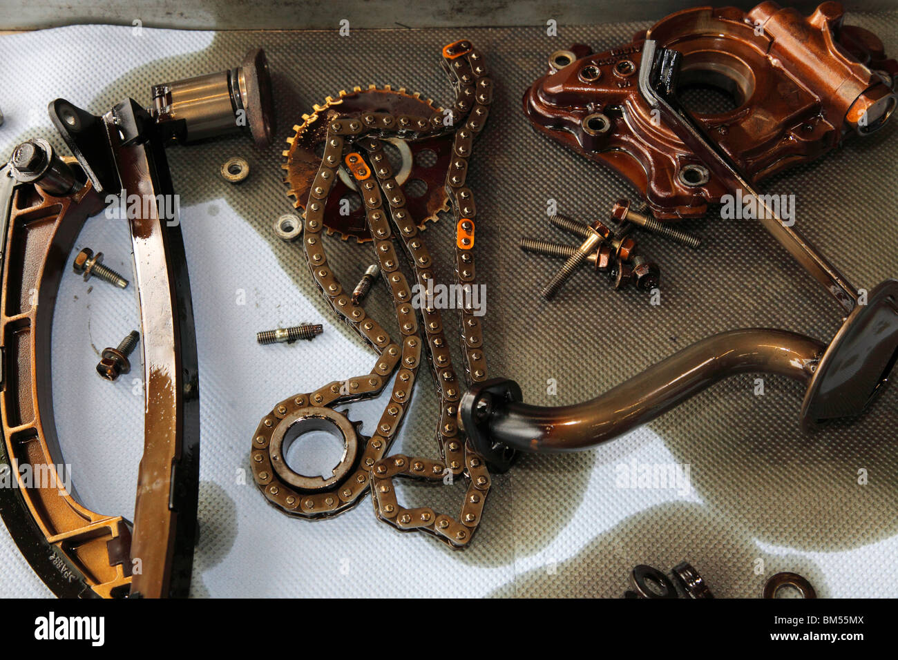 parts of a Toyota Avensis engine in an oilpan; engine changing after a product recall - Stock Image