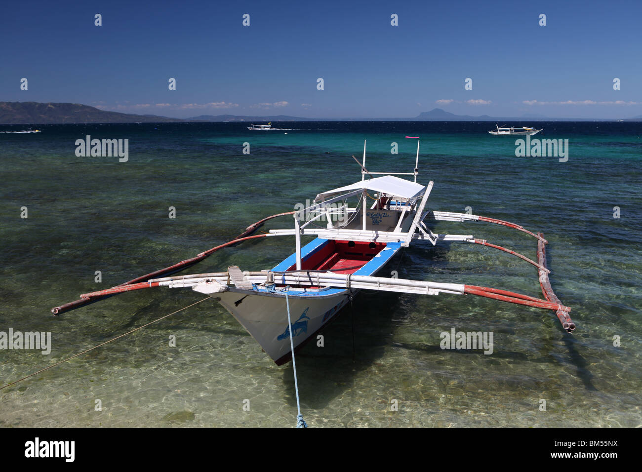 Boat moored off Small La Laguna Beach in Puerto Galera, located on the north of Mindoro Occidental in the Philippines. Stock Photo