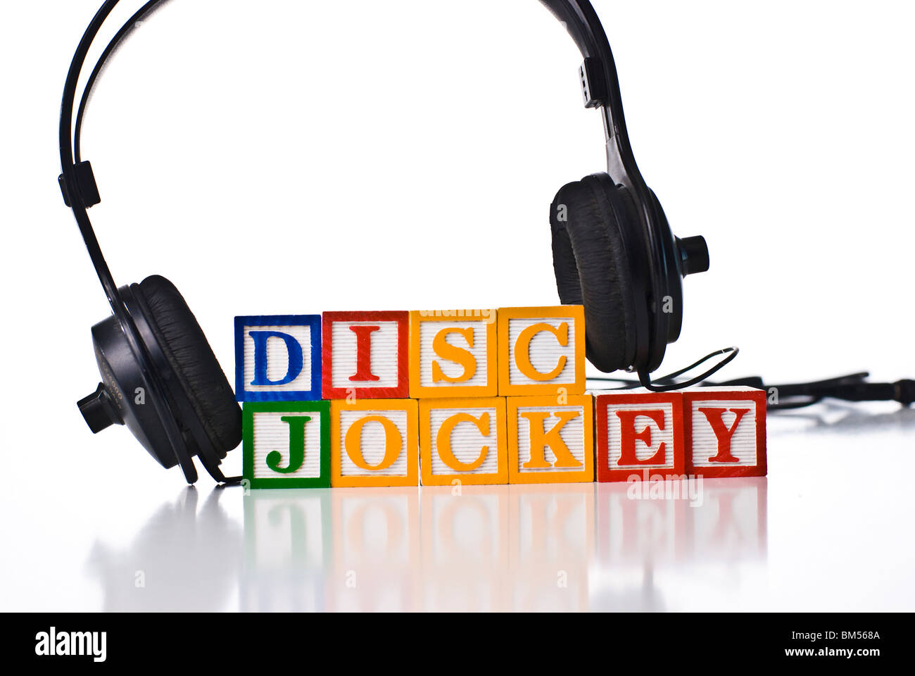 Colorful children's blocks spelling DISC JOCKEY with a set of headphones - Stock Image