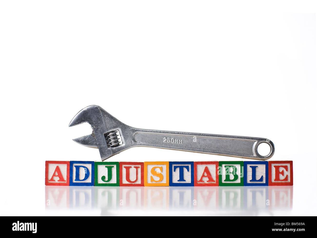 Colorful children's blocks spelling ADJUSTABLE with an adjustable wrench or spanner on top - Stock Image