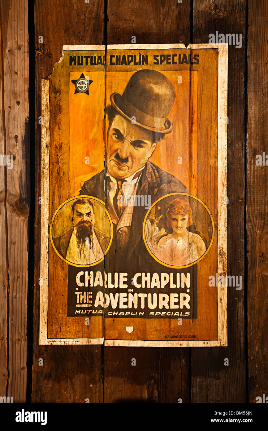 Poster on wood wall for Charlie Chaplin film The Adventurer - Stock Image