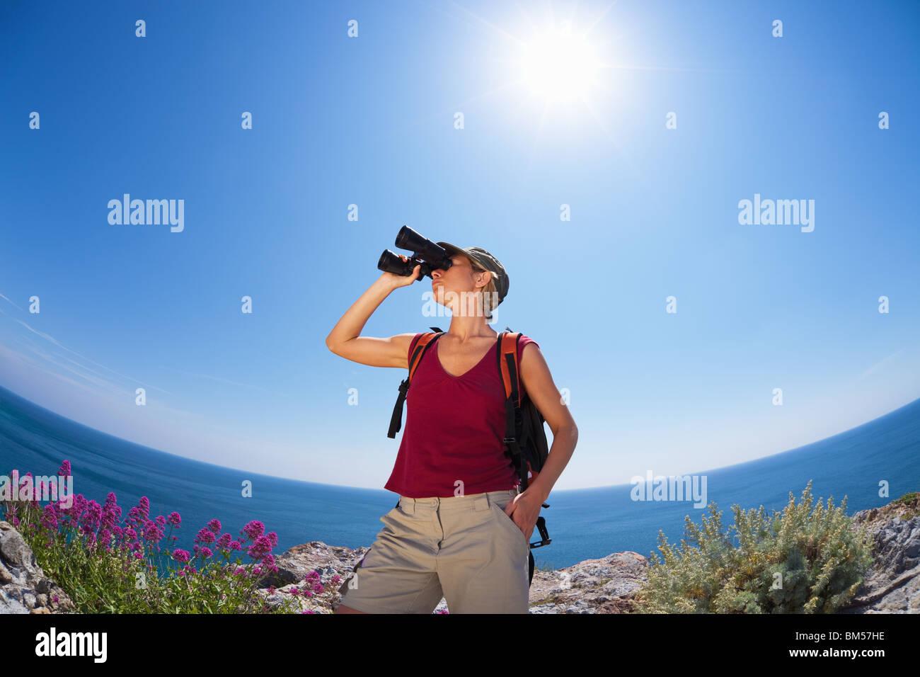 woman hiking and looking through binoculars - Stock Image