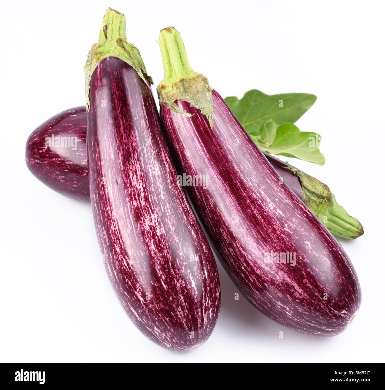 Purple eggplants with leaves on white background Stock Photo