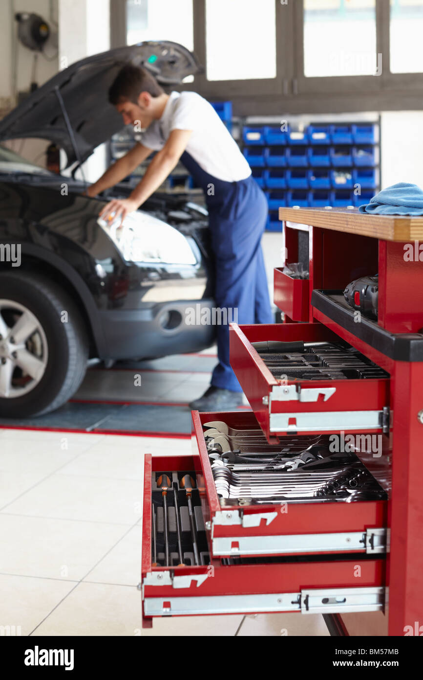 mechanic working on car engine. Focus on foreground - Stock Image