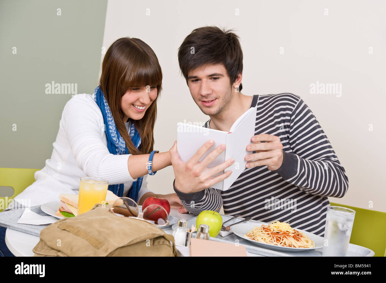Student cafeteria - Teenagers having lunch break, holding book - Stock Image