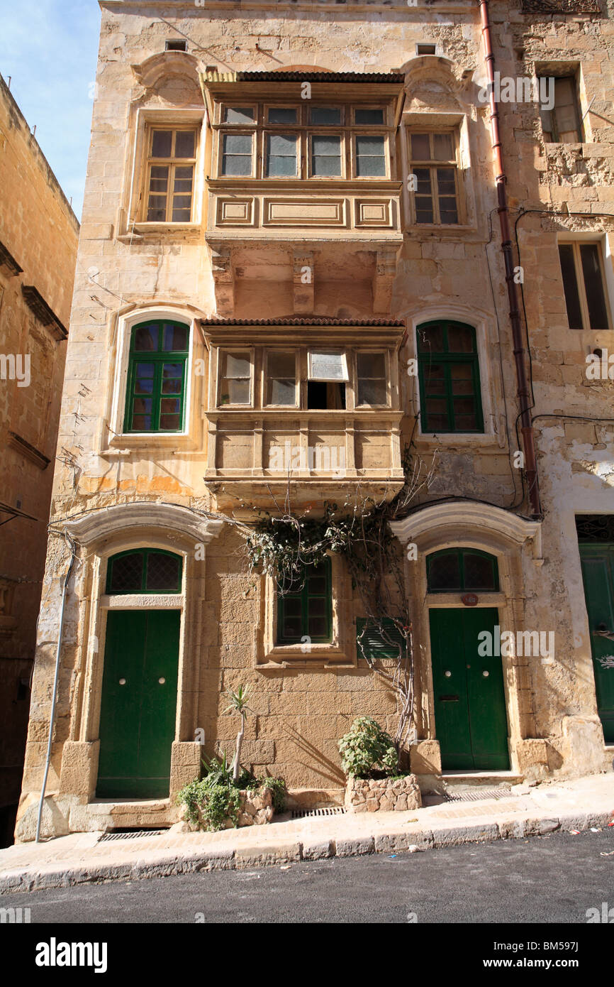 A traditional house in Valletta, Malta, showing the typical enclosed wooden balconies, arched doors and windows - Stock Image