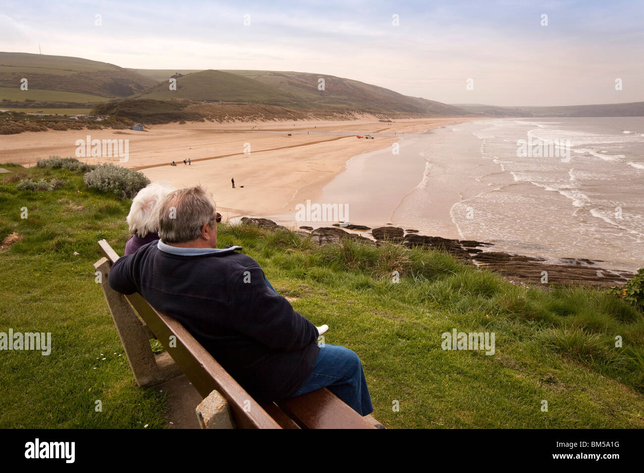 UK, England, Devon, Woolacombe, holidaymakers sitting on bench above the beach Stock Photo