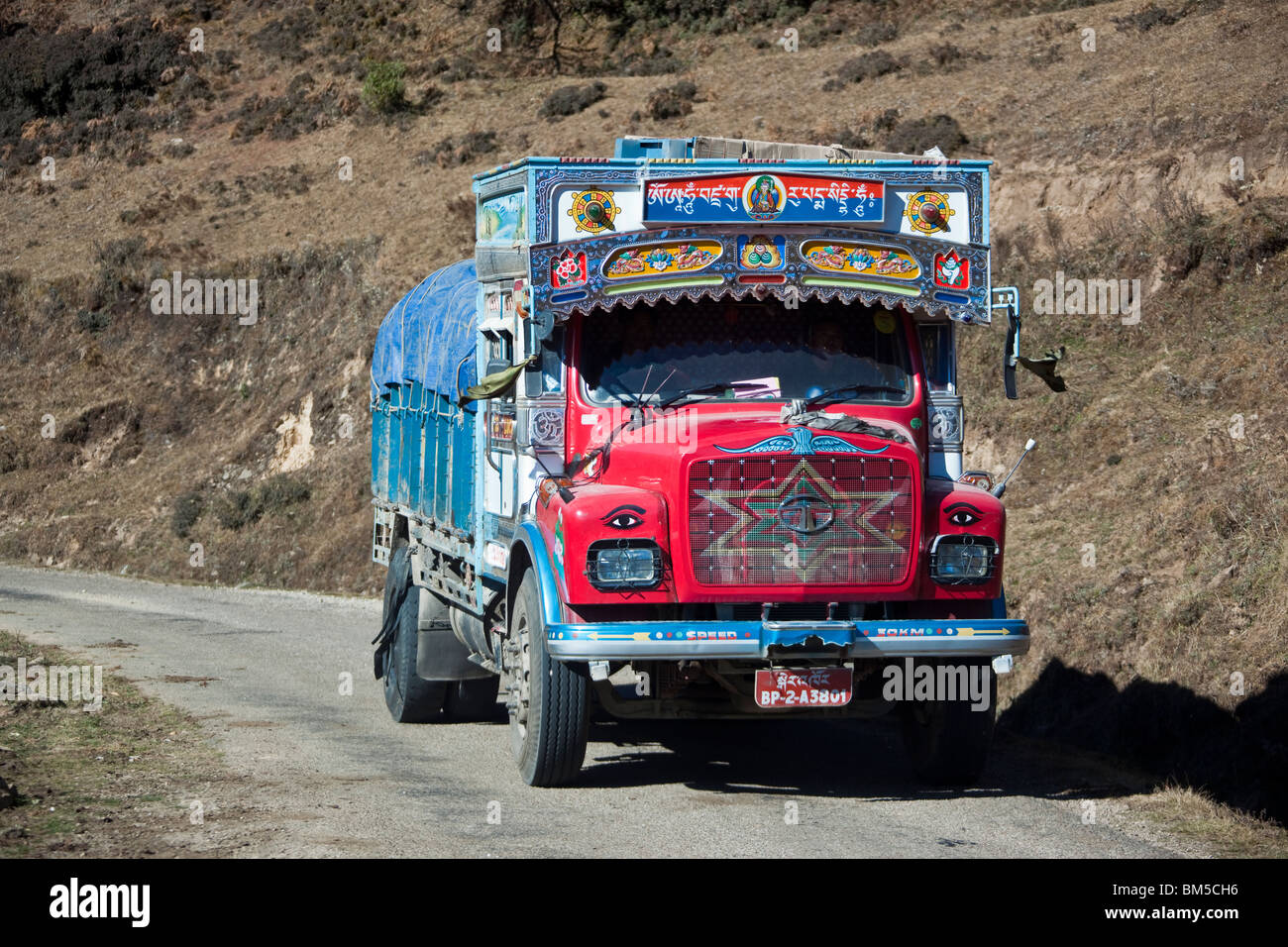 Decorated Tata truck hauling goods on the bhutanese national highway, Bumthang region, Bhutan - Stock Image