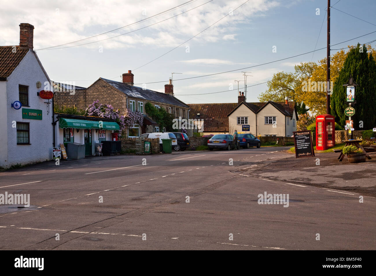 Centre of the village of Great Somerford, Wiltshire, England, UK with village shop or grocery store, red telephone - Stock Image