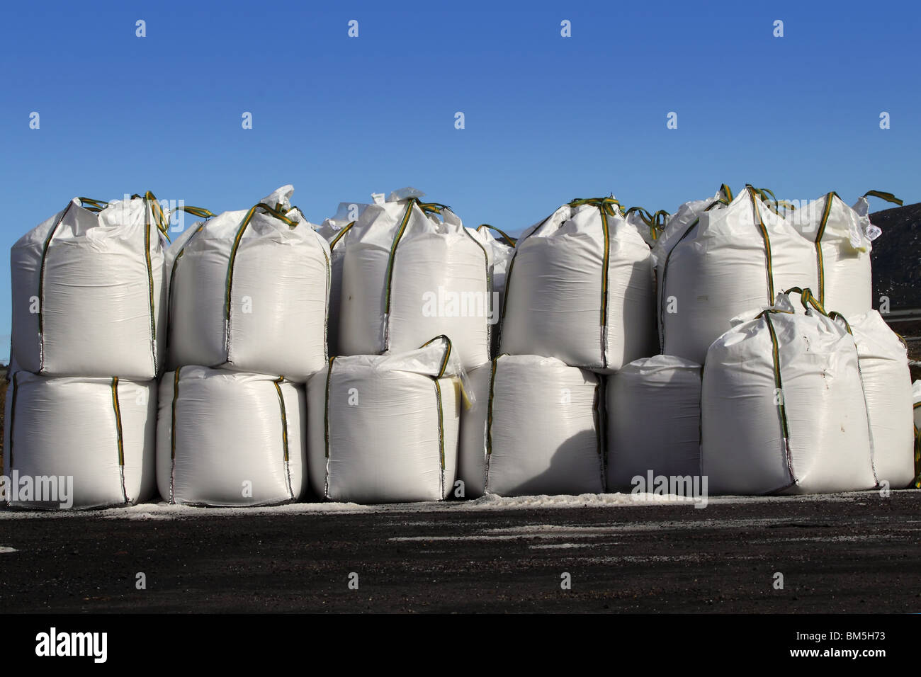 salt big bags sacks stacked rows for iced roads blue sky - Stock Image