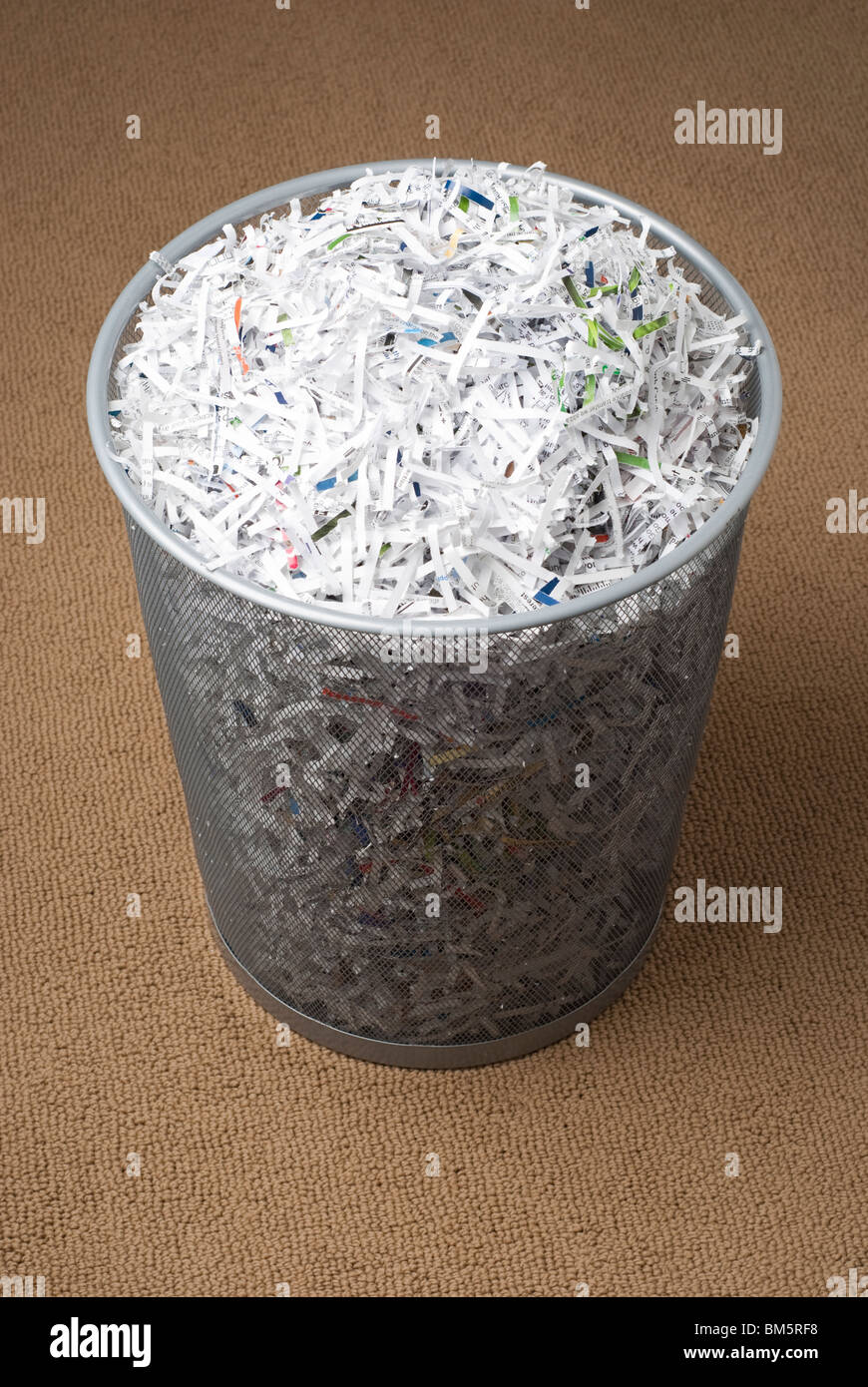 wastepaper basket filled with shredded paper on a carpet. - Stock Image