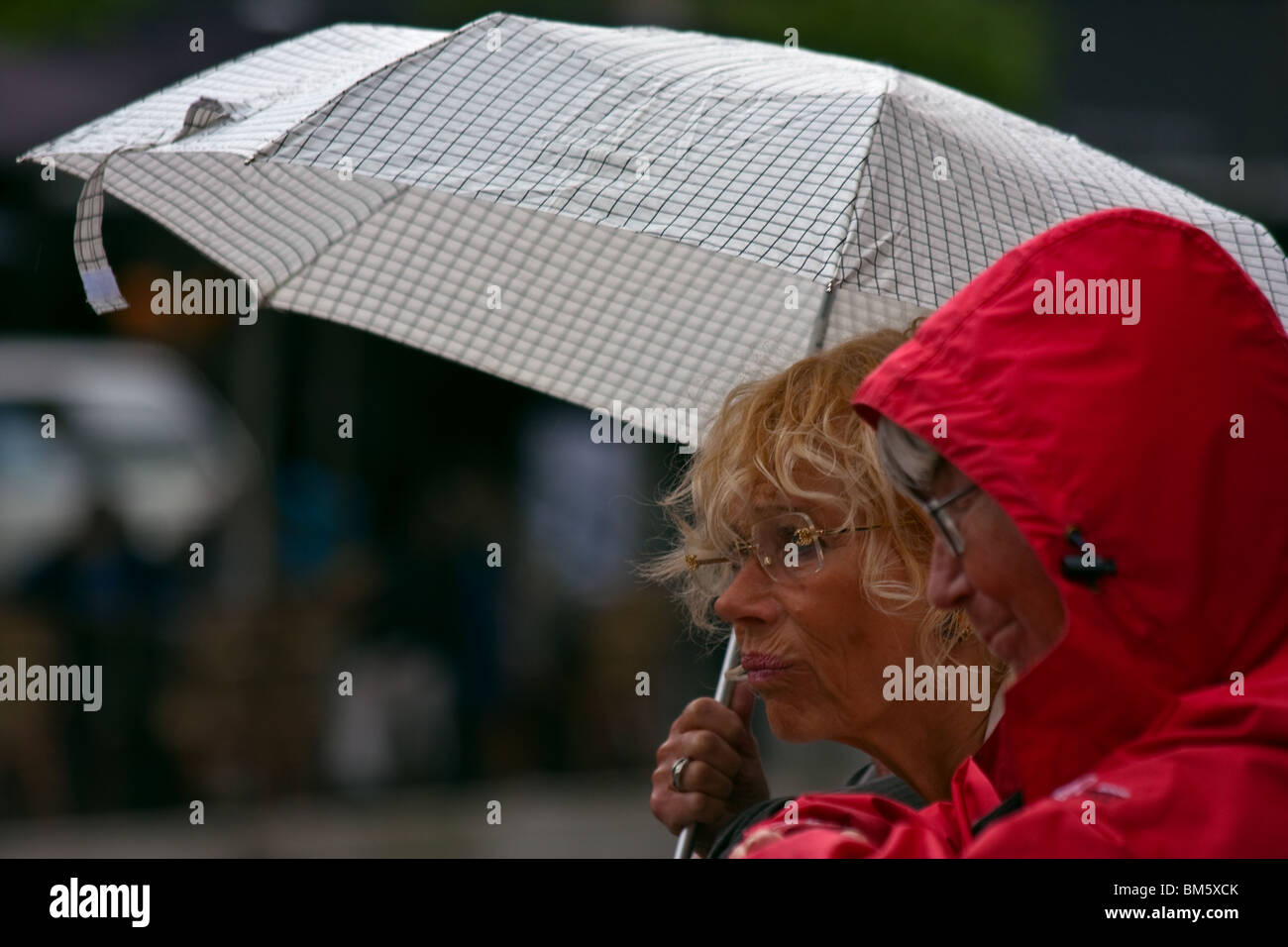 women shopping on a rainy day, annoyed over the weather Stock Photo