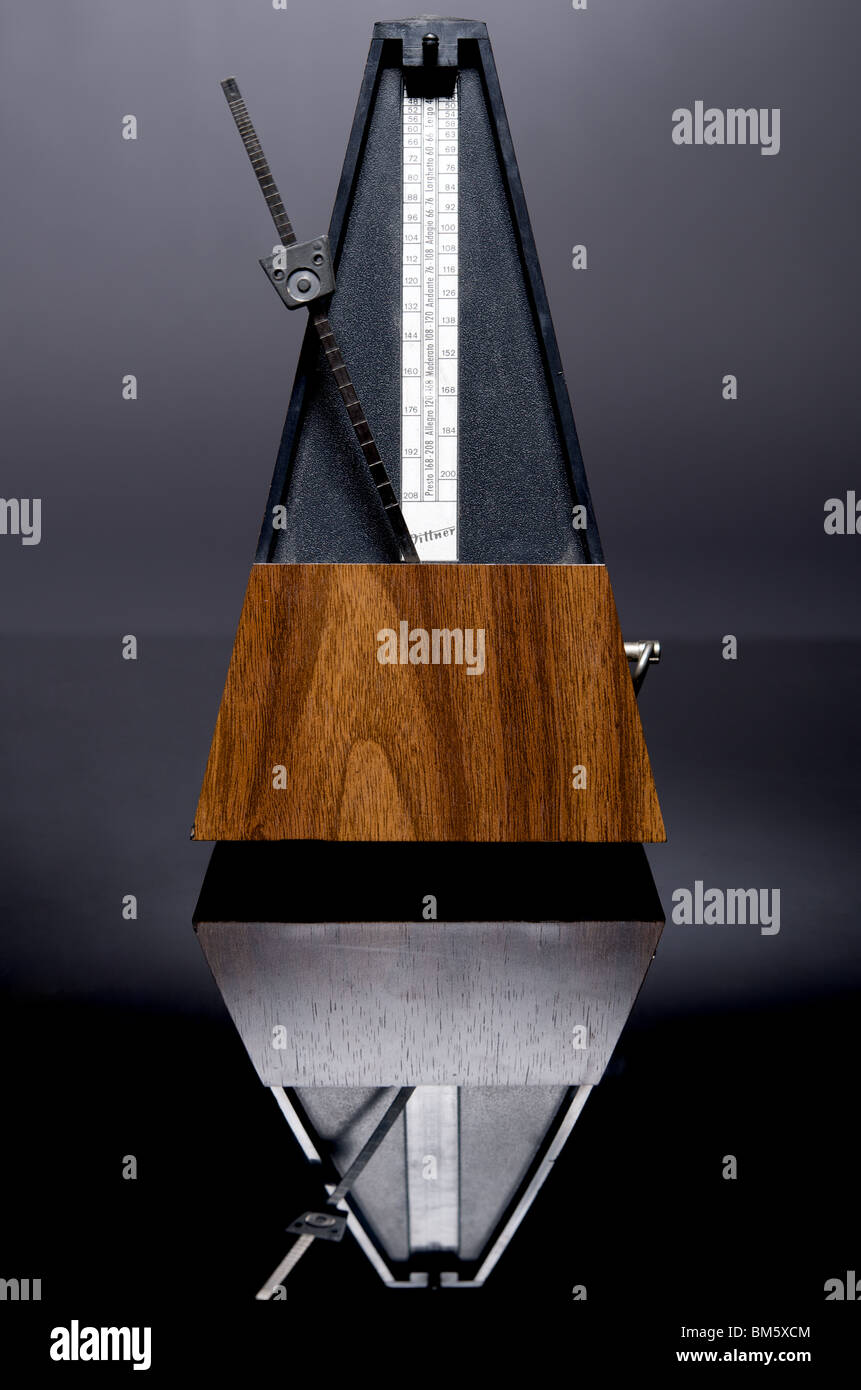 Photo of wooden clockwork metronome with bar-marking bell, ticking, with reflection in black perspex - Stock Image