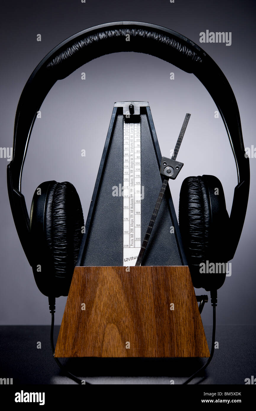 Photo of clockwork metronome wearing a pair of padded headphones, against a grey background - Stock Image