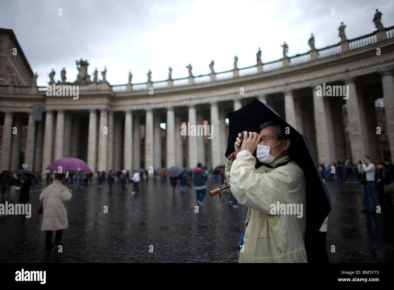 A tourist takes a picture in the rain in Saint Peter's Square in Vatican City, Rome, March 10, 2008. Photo/Chico Stock Photo