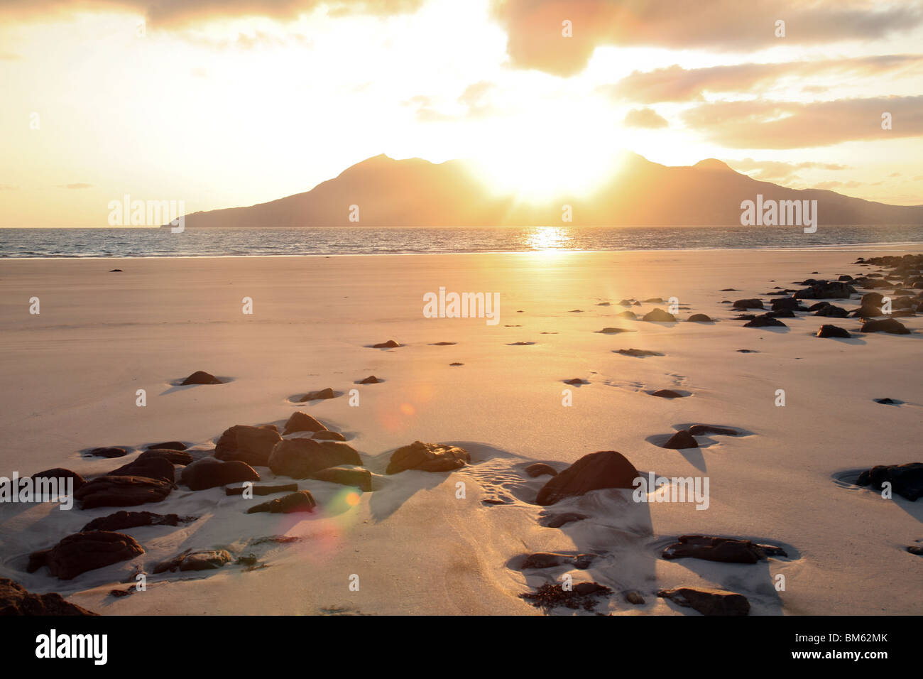 Sunset over the Isle of Rum, seen from Laig Bay, the Isle of Eigg, Western Isles, Scotland, UK - Stock Image