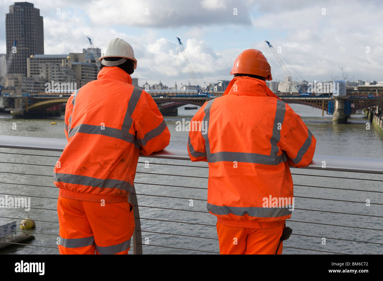 Two workmen in orange high visibility jackets - Stock Image
