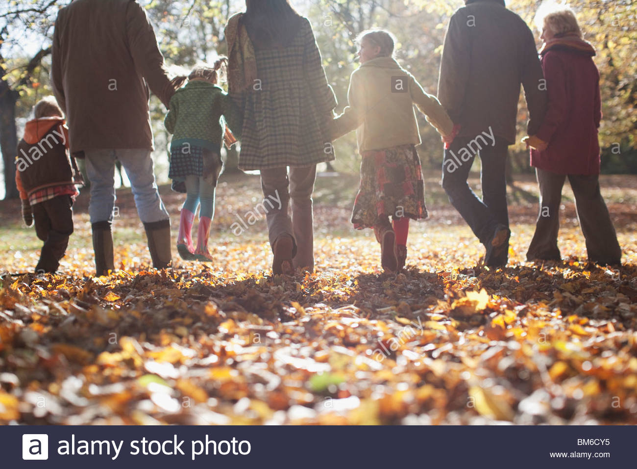 Extended family holding hands and walking outdoors - Stock Image