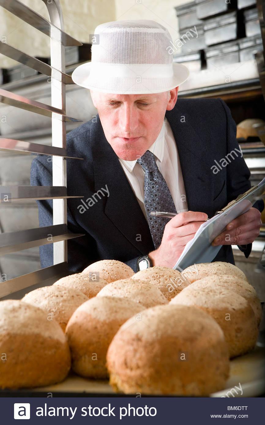 Inspector examining fresh loaves of bread - Stock Image