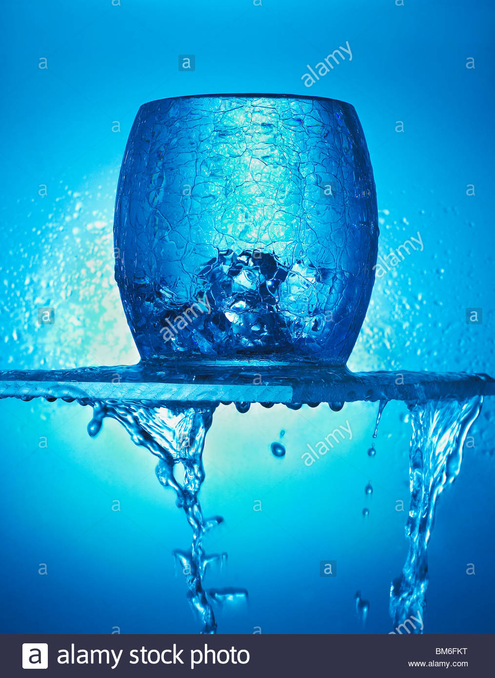 Close up of blue glass, ice cubes and dripping water - Stock Image