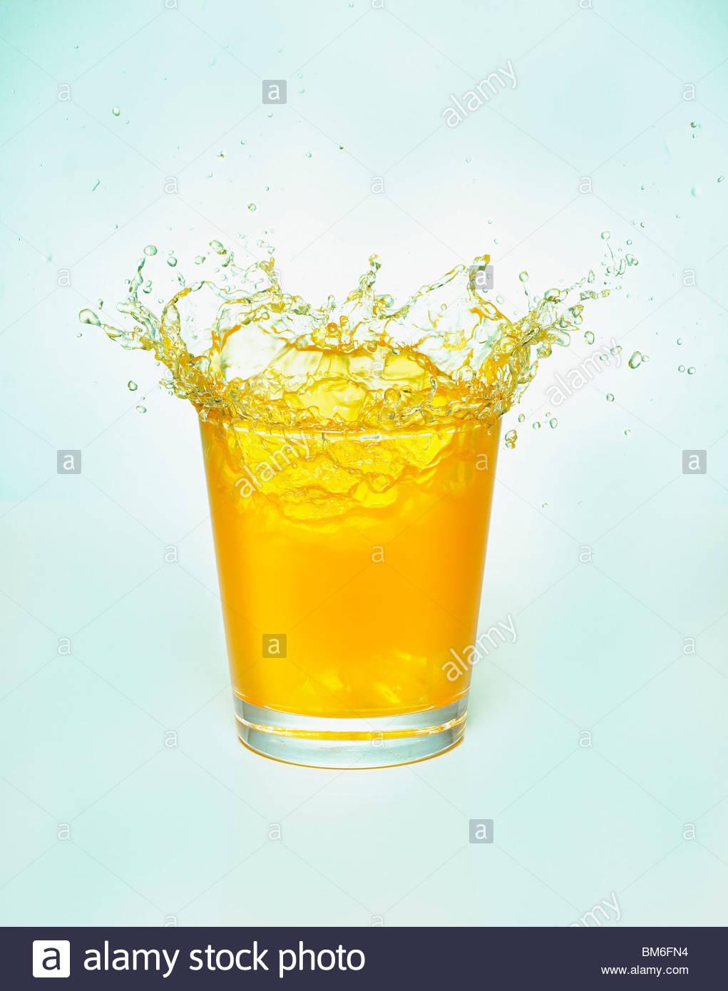Close up of orange juice splashing out of glass - Stock Image