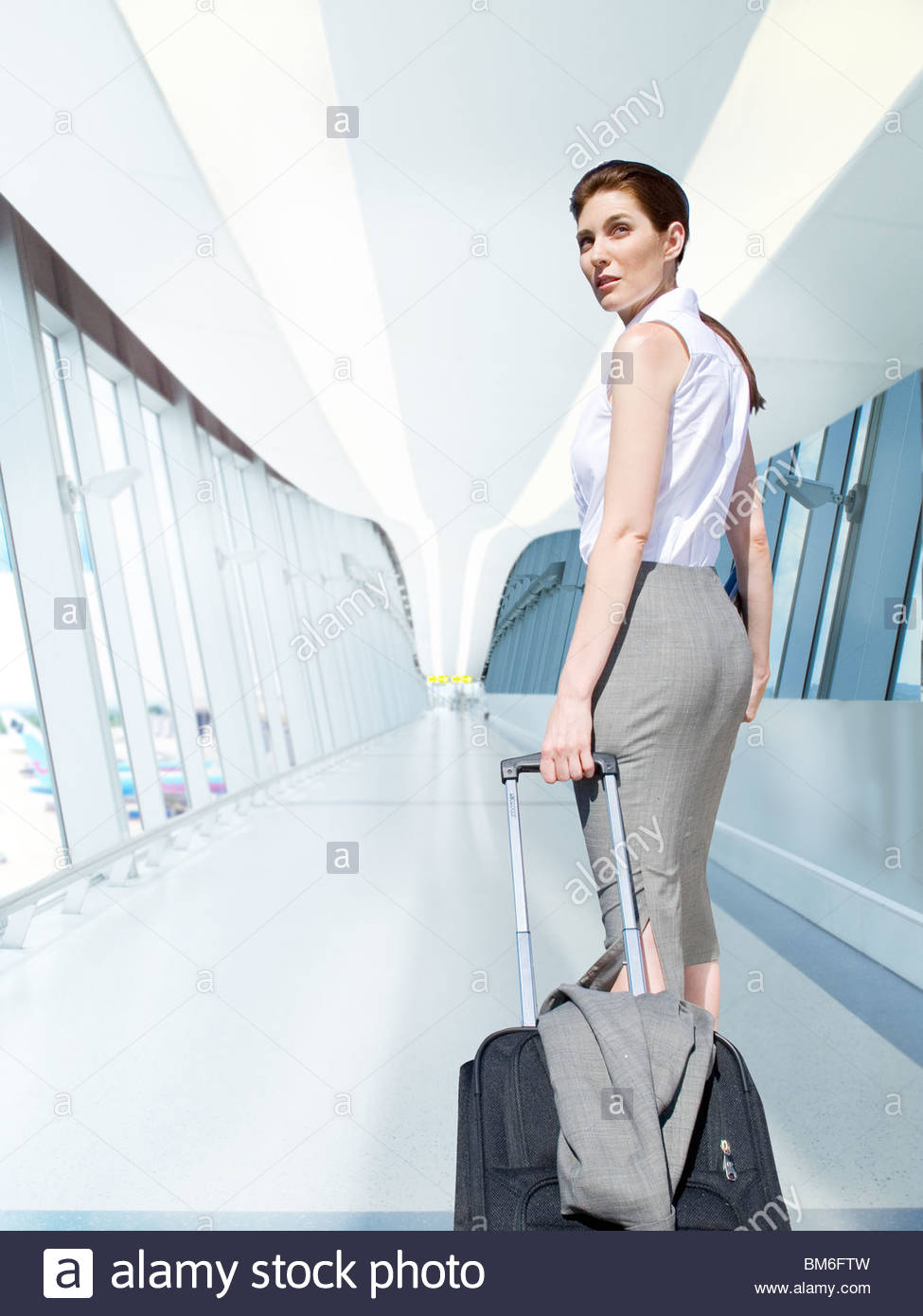 Businesswoman pulling rolling luggage in airport concourse - Stock Image