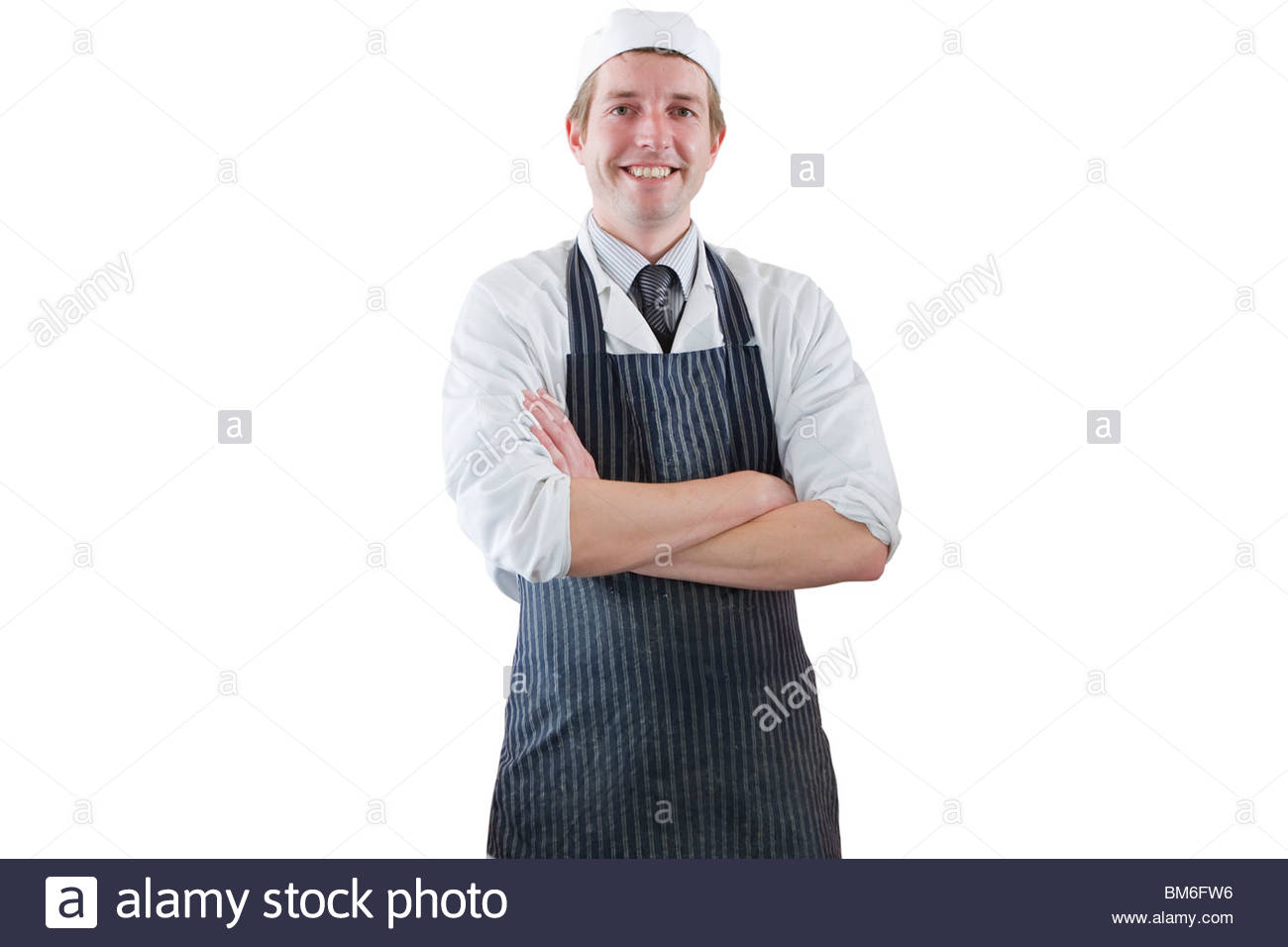 Smiling butcher with arms crossed in apron and cap - Stock Image