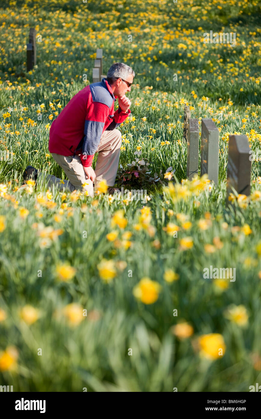 A mourner at a grave side in Troutbeck church in spring, Lake District, UK. - Stock Image