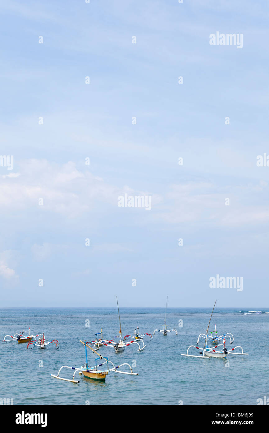 Traditional outrigger fishing boats in the ocean at Sanur, Bali, Indonesia - Stock Image