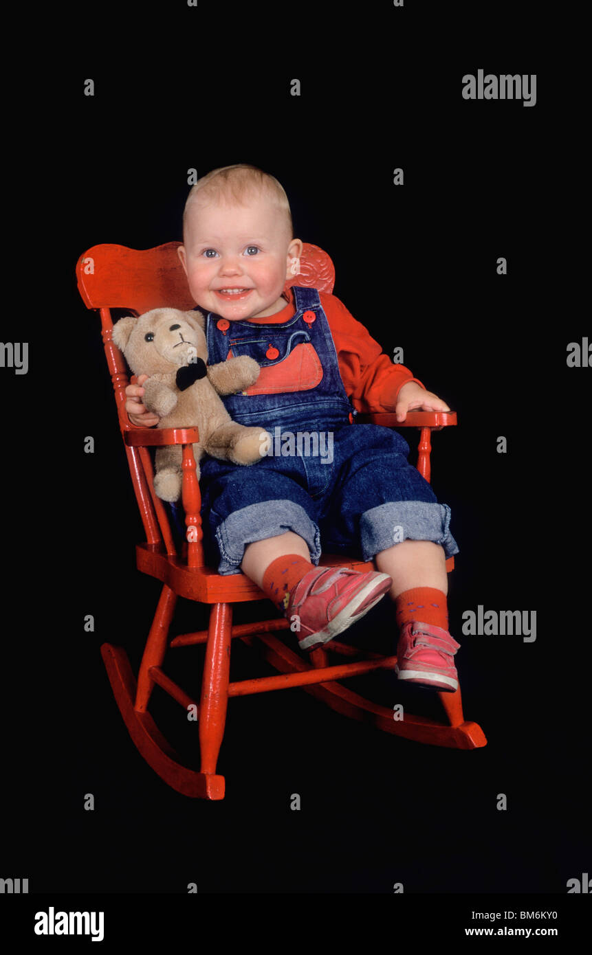 Toddler Sitting In Red Rocking Chair With Teddy Bear Stock