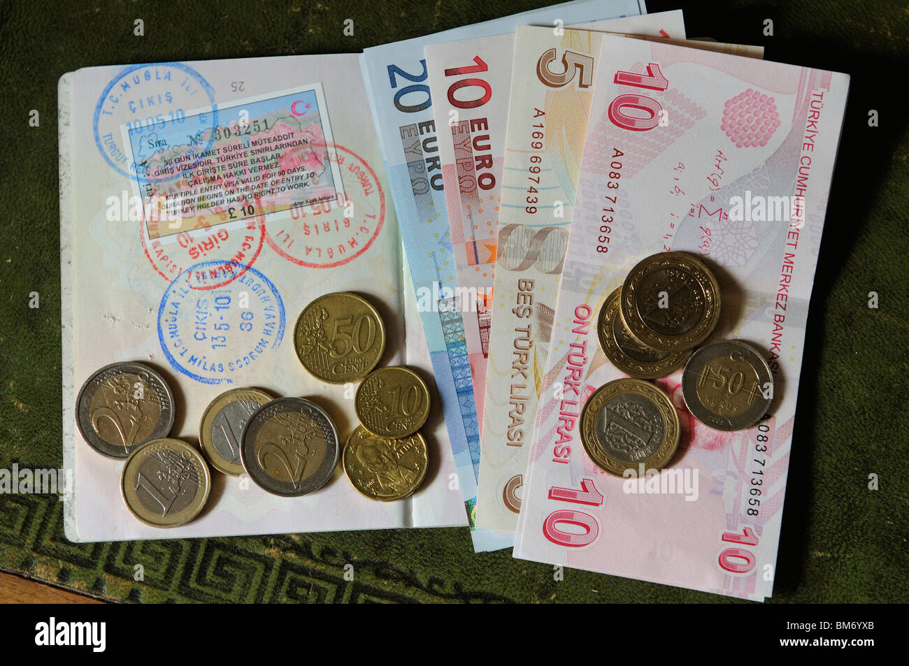 Turkish 90 day multiple entry visa in UK passport with entry and exit stamps and coins and Turkish Lire banknotes& - Stock Image