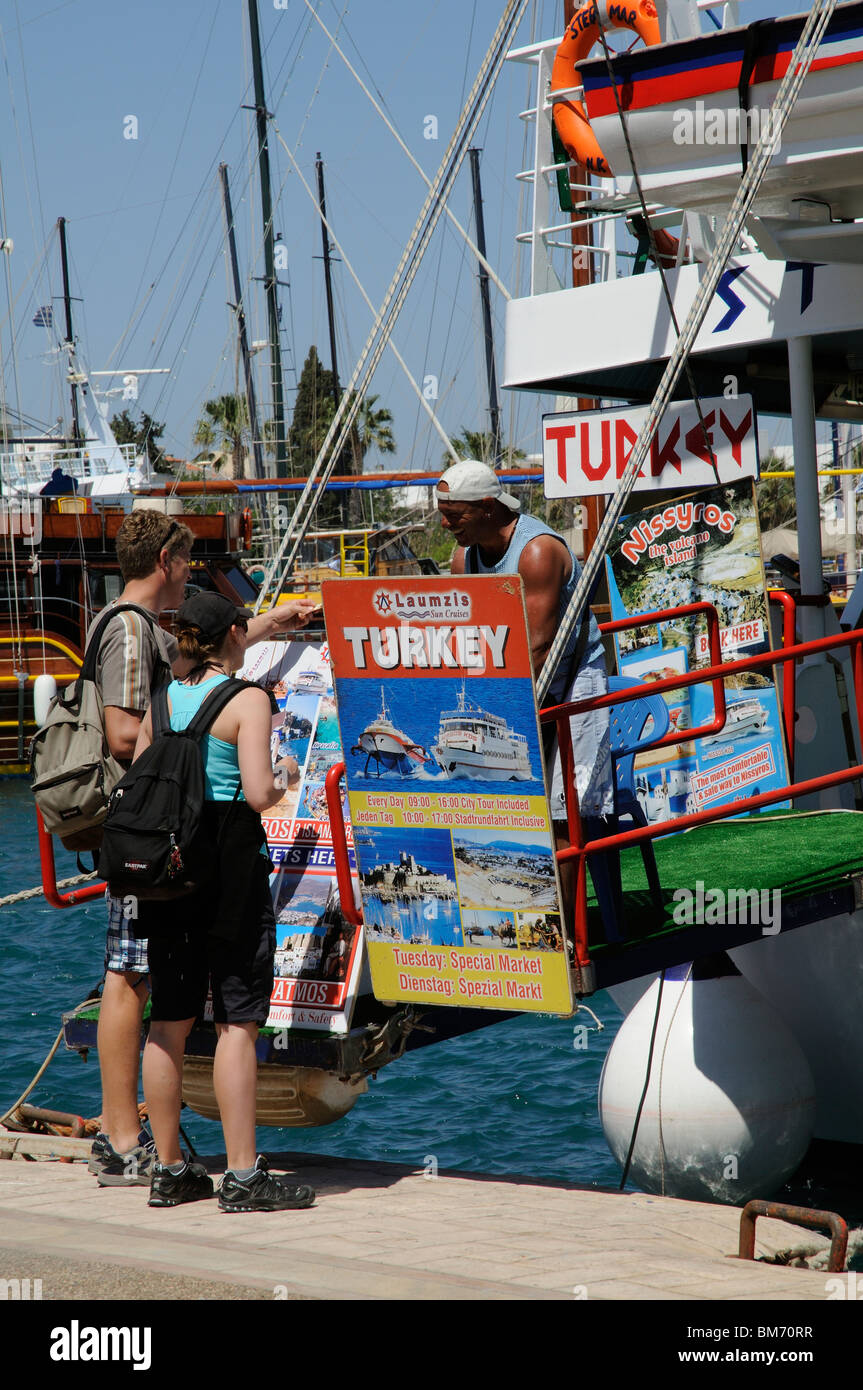 Holidaymakers on the quay in Kos Town Greece booking a boat trip to Bodrum Turkey Couple paying for their ferry - Stock Image